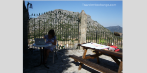 writer sitting at an outdoor table with laptop and books
