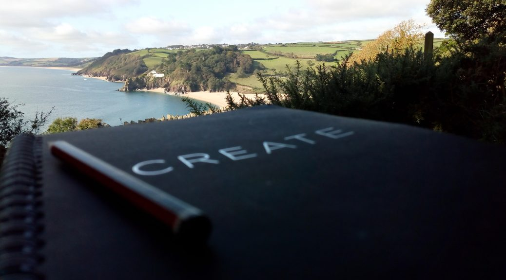 A notebook outdoors with the a view of the sea in the background