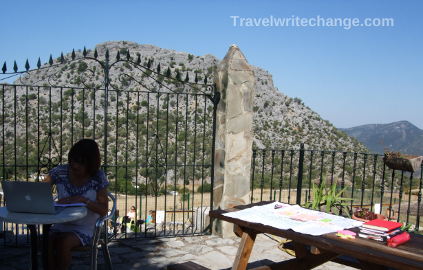 Writer at an outdoor table on a writing retreat in Spain