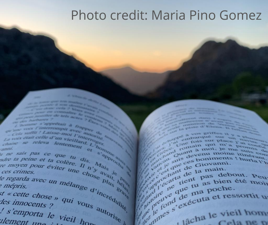 Open book with a background view of the Spanish mountains. Writing courses