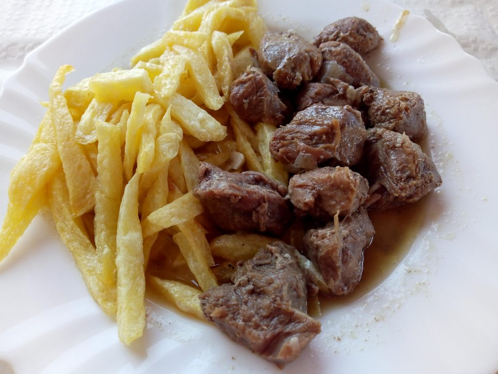 a plate of meat and homemade chips